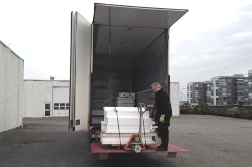 Lastbil med baklift och handtruck.