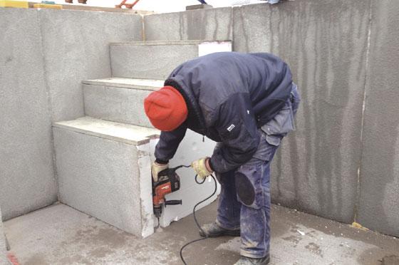 Expanderbult skruvas fast i betongplattan.