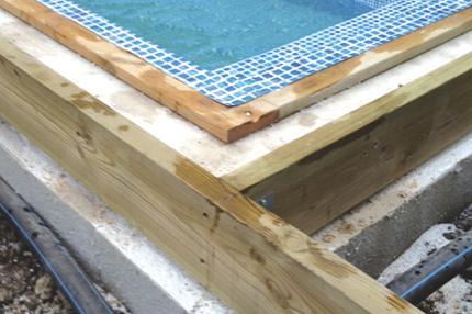 Cellplasten skärs ner och träreglar fästs runt poolen.